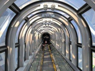 No interior da escada rolante coberta por vidro. É tida como a mais alta escada rolante do mundo, e oferece grandes vistas da cidade enquanto flutua no espaço.
