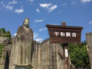 A lone visitor stands under the Peace Kannon