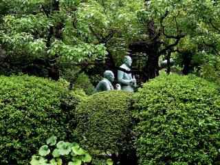 Statues of Yamazaki whiskey Distillery's founders stand in the well manicured garden