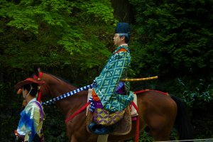 An archer on horseback parades through the crowd