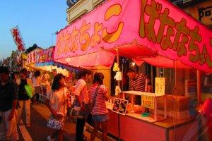 Food vendors light up for the evening crowds, filled with all kinds of interesting taste sensations