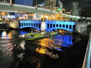 Sebuah bus air meluncur melalui ruang kecil antara air dan Jembatan Nishiki melewati Sungai Tosabori... mendebarkan sekali!