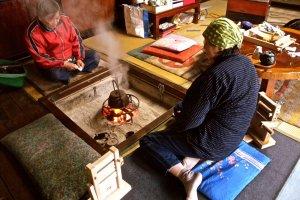 Enjoying the warmth around the irori, where Mrs. Sato prepared my tea