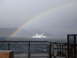Un arc-en-ciel créé par le temps humide passe au dessus du ferry et de Sakurajima