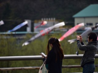 คนคู่นี้ยืนถ่ายรูปริ้วประดับปลาคาร์ฟอยู่บนสะพาน