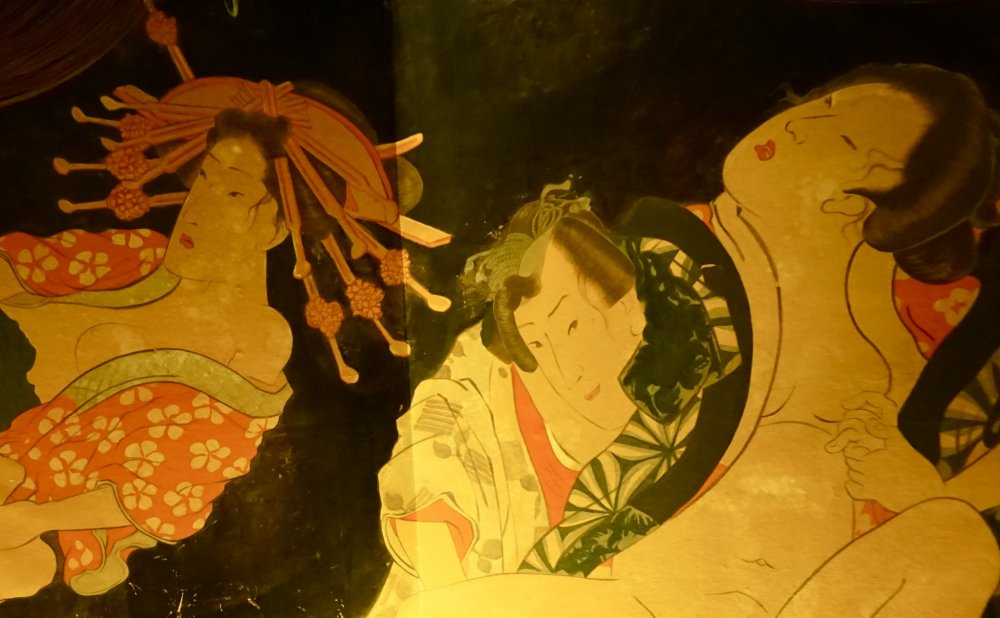 "The painting on the wall is also known as ""Shunga,"" a type of erotic ukiyo-e that developed in the Edo Period."
