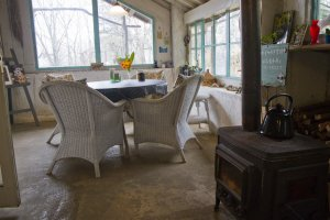 The sunroom is heated with a woodburning stove in winter and looks out into the gardens
