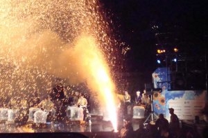 The hand-held fireworks light the taiko drums behind