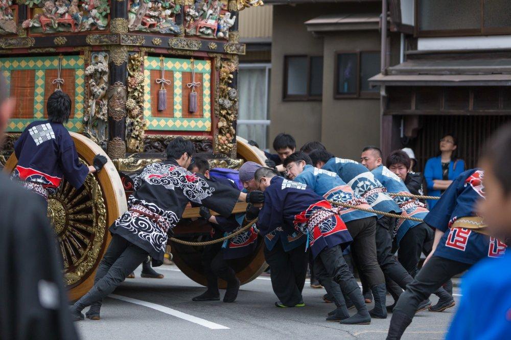 Des festivaliers poussent sur les chars afin qu'ils ne s'écrasent pas en bas de la pente