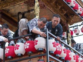 Des festivaliers attachent les lanternes sur les chars
