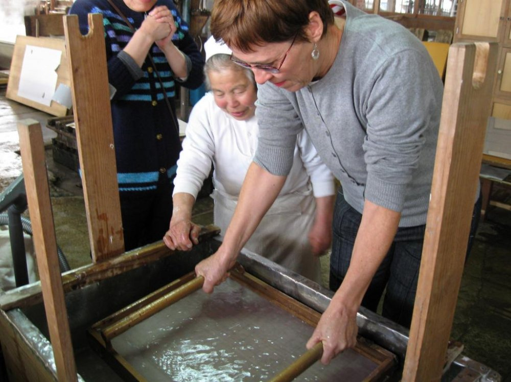 The women at the Ikazaki workshop can show you how to make your own sheet. The first step is the hardest: the pulp must be evenly spread over the screen. The women handle the heavy screens with skill and dexterity.
