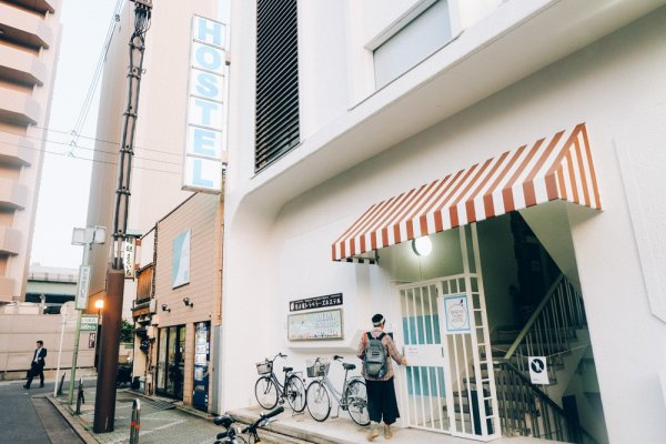 "The exterior of Nagoya Travellers. Spot the big signage of ""Hostel"" and usually there are lots of bicycles parked outside the building."