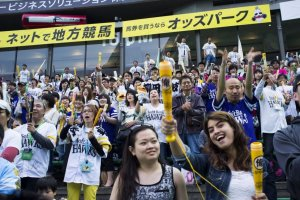 Enthusiastic Fukuoka SoftBank Hawks fans, armed with plastic bats, cheer their home team on.