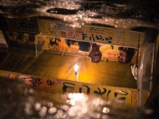 Reflet d'un stand de nourriture dans une flaque