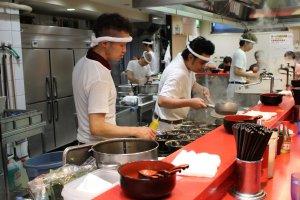 Chefs hard at work preparing a dozen ramen servings at once.
