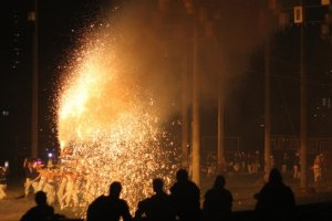 The crowd watches as the men bathe themselves in firework sparks.