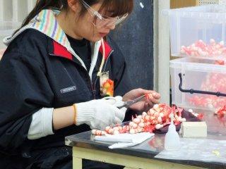 An employee at Sample Kobo makes plastic food replicas of shrimp tempura