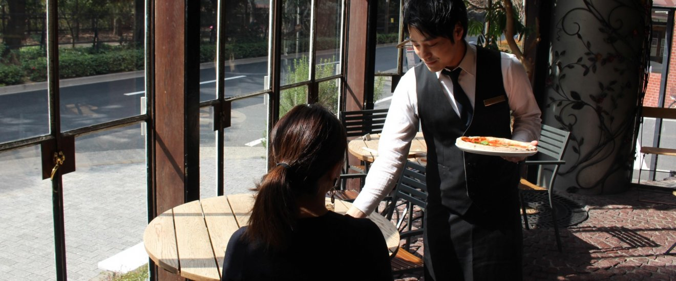 Server presenting a lunch pizza