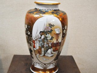 A vase in the museum complete with beautiful artwork.