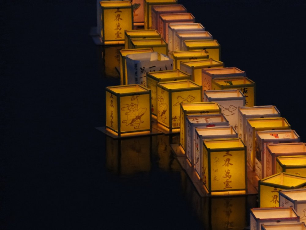 Les lanternes flottent sur la rivière pour marquer la fin d'Obon