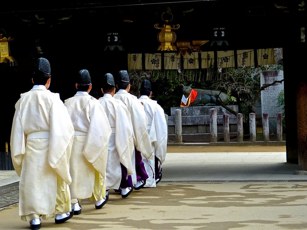 Just before the start of a ceremony, Shinto priests walk into the sanctuary