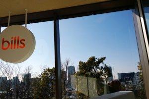 หนึ่งในมุมมองจากภายในร้าน Bills ที่ทำให้เราเห็นวิวสวนเก๋ๆ บนดาดฟ้า พร้อมวิวเมืองโตเกียวในมุมสูง ซึ่งในวันที่อากาศดีๆ ท้องฟ้าปลอดโปร่ง บนชั้นดาดฟ้านี้ยังสามารถเห็นวิวของภูเขาไฟฟูจิได้อย่างงดงามอีกด้วย