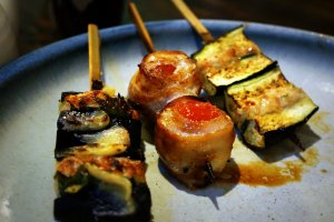 Pork wrapped tomato flanked by tsukune stuffed eggplant.