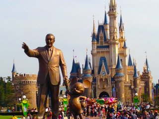 Walt Disney with his partner Mickey Mouse and the Cinderella Castle in the background