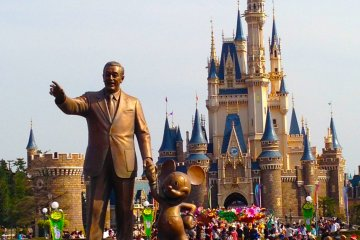<p>Walt Disney with his partner Mickey Mouse and the Cinderella Castle in the background</p>