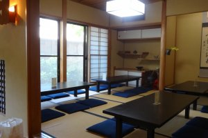 The back room with small tables on tatami floor looking out into an outside garden