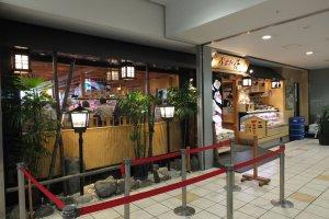 ด้านหน้าของร้านพร้อมที่กั้นแถวต่อคิวในช่วงเวลากลางวันและเย็น