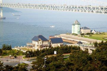 배경으로 두 개의 역사적 건물 (왼쪽 : 이전 무토 산지 거주지, 오른쪽 : 선얏센 기념관)과 아카사 해협 대교 (일명 : 펄 브리지)