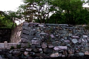 <p>Colorful stone wall, with pink, blue, green-like color stones</p>