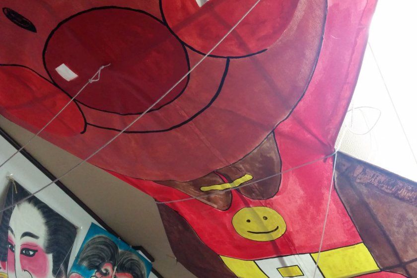 An Anpanman character hovers over the workbench at the Kesennuma kite club's storage building