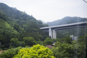 Elevated train tracks nestled among beautiful mountains on the journey from Hachioji to Matsumoto