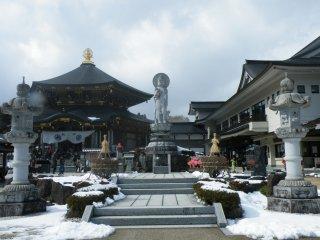 本堂には阿弥陀如来の宝軸が保管されている (左側)。中央に建っているのが子育観音だ