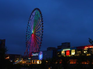 The 115 meter high Ferris Wheel outside Venus Fort, lit up against the night sky. A complete revolution of the wheel takes about 15 minutes, and offers views of Odaiba and the Tokyo Bay.