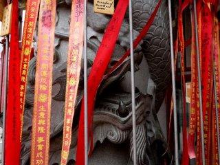Một pho tượng rồng lấp sau những dải ruy băng màu đỏ