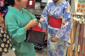 <p>While sporting a Rakuchin Kirei Yukata, I was then introduced to a Kago-Kinchaku (purse made of bamboo and fabric to keep a PET bottle and other small personal belongings secure.</p>