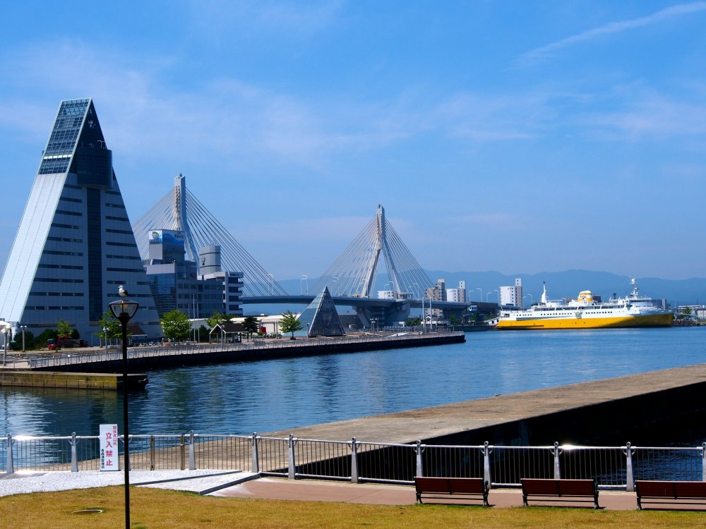 From Aoi Umi Kōen, you can see all along Aomori Bay -- in view are the ASPAMbuilding, the Aomori Bay Bridge, and the Memorial Ship Hakkoda-Maru