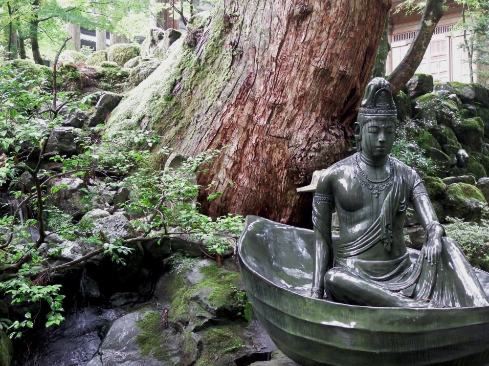 Statue of Goddess of Mercy sits in a boat in a small pond in front of the entrance gate