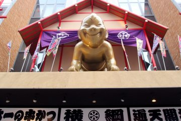 Billiken, a God of Good Luck or Happiness smiles down at me.