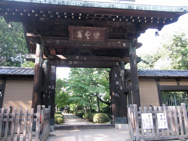<p>After walking on a long pathway to get away from the neighborhood, you reach the large, main gate to the temple.</p>