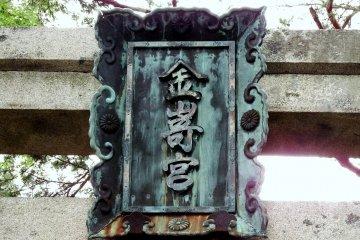 <p>Bronze signage of Kanegasaki Shrine hanging on the torii gate</p>