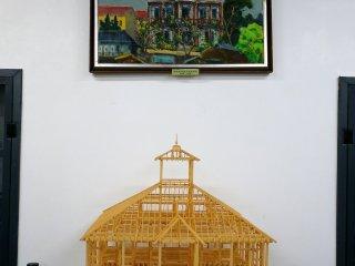 Một mô hình khung gỗ của tòa nhà đứng dưới một bức tranh theo trường phái ấn tượng