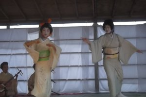 Geisha dancing on the outside stage; the orange headband makes her a pumpkin, the other is the eggplant