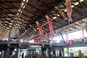 海彩館中央の吹き抜け部分には市場の水槽が設置されていて、天井からは5月のこどもの日の後だったこともあり、こいのぼりと大漁旗が飾られていた。