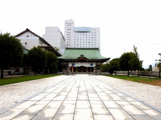Looking at the main shrine building from the top of the stairs. The Hotel Fujita Fukui is towering over it
