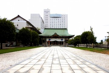 계단 꼭대기에서 주요 사당 건물을 보는 것. 후지타 후쿠이 호텔이 그 위로 우뚝 서 있다