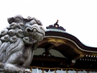 Stone guardian lion and the shrine roof under a cloudy sky